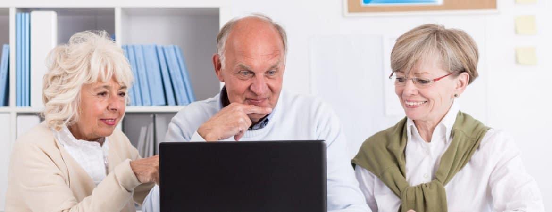Zu sehen sind zwei ältere Frauen und ein älterer Herr, die alle drei vor einem Laptop sitzen.