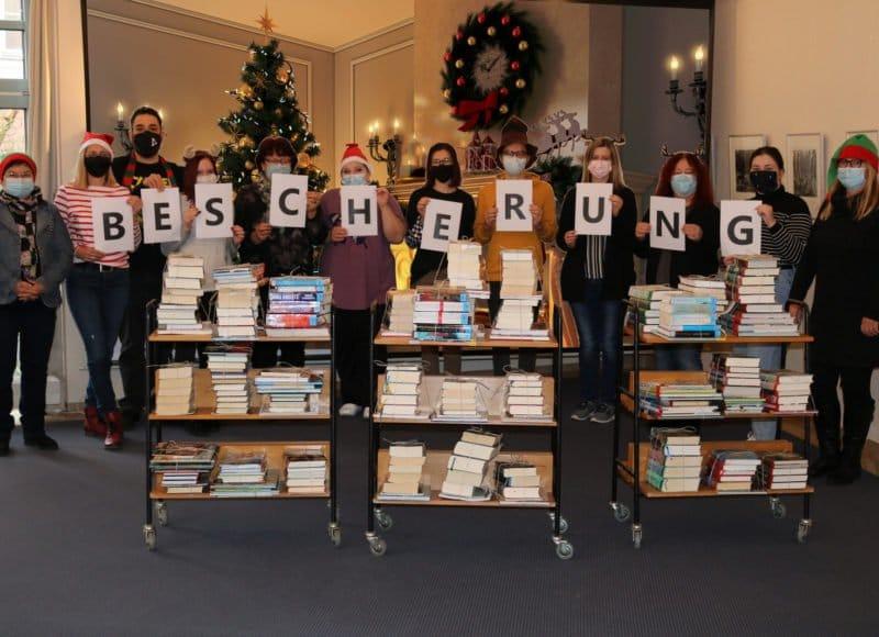 """Das Team der Stadtbibliothek Deggendorf steht hinter den geschnürten """"Bibliothek to go""""-Paketen und halten Buchstaben in der Hand, die das Wort """"Bescherung"""" verdeutlichen."""